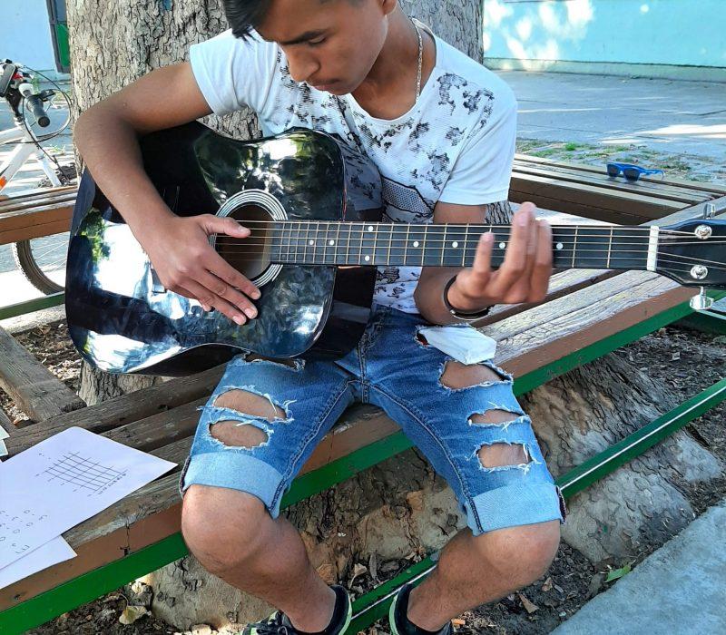 Ramadan (14), practicing guitar playing in Klisa